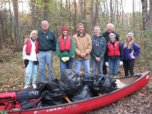 Volunteers with pile of trash bags in a canoe at Blackstone Canal