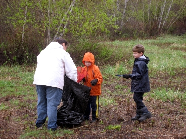 Young volunteers loading a trash bag